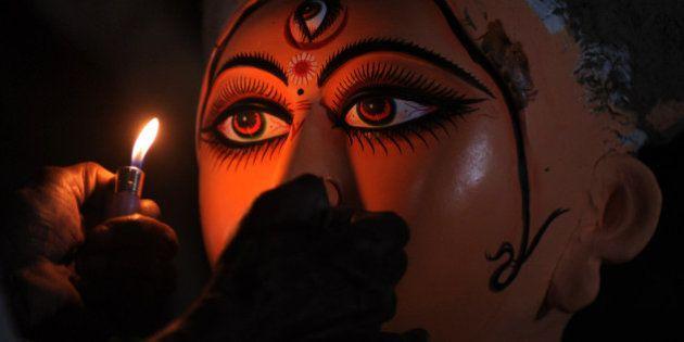 An Indian idol maker draws eyes onto a clay statue of Hindu goddess Durga, in Kumartoli, the idol makers...