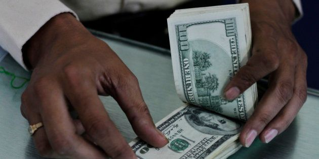 An Indian man counts U.S dollars at a Western Union money transfer center in Ahmadabad, India, Monday,...