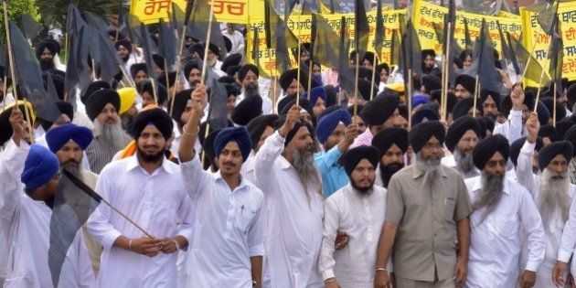 Activists from The Shiromani Gurdwara Parbandhak Committee (SGPC) hold black flags as take part in a...