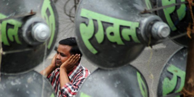 A Indian man protects his ears with his hands as he passes a display of 144 loudspeakers during a Dusshera...