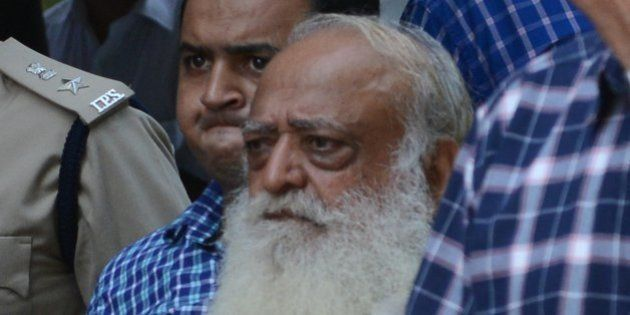 Indian spiritual guru Asaram Bapu (C, in white) is escorted by state police as he arrives at a local...