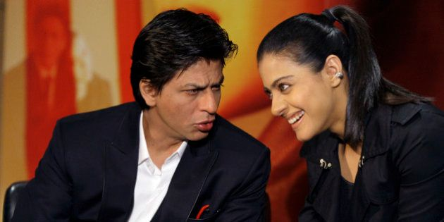 Indian actors Shah Rukh Khan, left, and Kajol Devgan talk to one another during a press conference as...