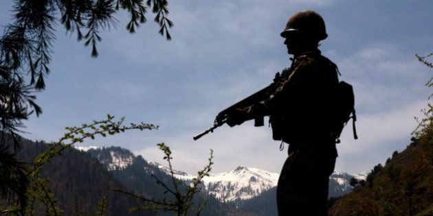 GOHALAN, KASHMIR, INDIA - APRIL 20: An Indian army soldier is silhouetted against the snow capped mountains...