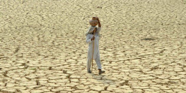An Indian man carries a clay pitcher of water on his head as he crosses parched land on a hot day at...