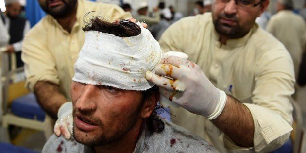 Pakistani paramedics treat a man injured in an earthquake at a hospital in Peshawar on October 26, 2015....