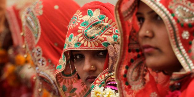In this Saturday, March 21, 2015, photo, a bride adjusts her veil during a mass marriage ceremony in...
