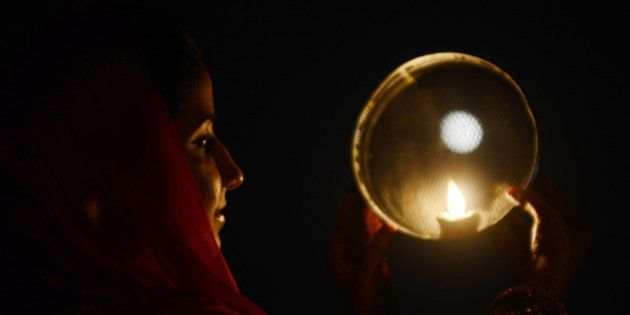 An Indian Hindu woman poses while performing a ritual on the occasion of the Hindu festival of Karva...
