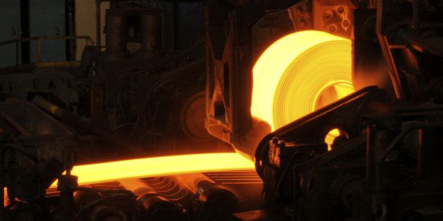 Hot orange steel rolling process in a steel manufacturing industry. Hot rolling is a metalworking process...