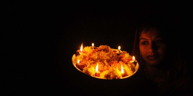 Indian woman Chanda poses with earthenware lamps on the eve of the Hindu festival of Karva Chauth (Husband's...