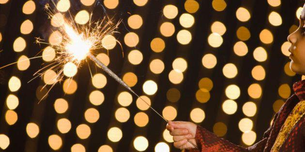 Boy (4-5) holding flashing sparkler during Diwali