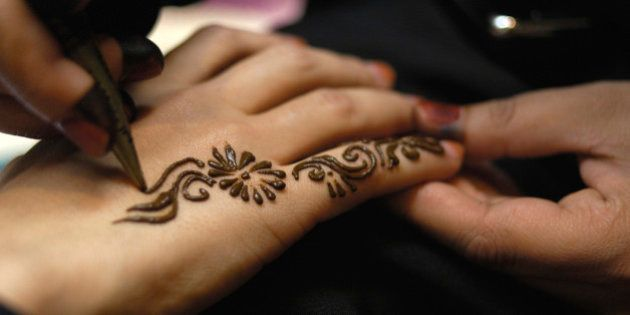 United Arab Emirates, Dubai, applying henna pattern to woman's