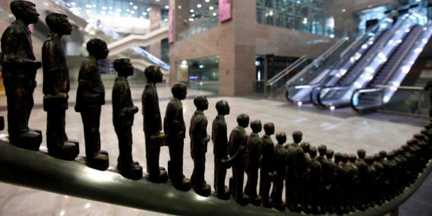 Sculptures in the likeness of passengers stand on display at the Delhi Metro Airport Express Line station...