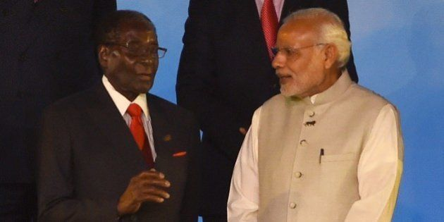 Indian Prime Minister Narendra Modi (R) speaks with Zimbabwe's President Robert Mugabe during the group...