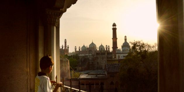 Child staring at Badshahi Mosque, Lahore from Lahore Fort at sunset. Both of the buildings are artistic...