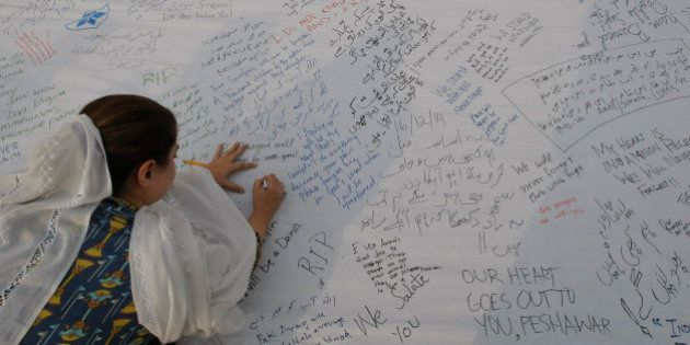 A Pakistani girl writes a message for students killed in a Dec. 16 Taliban attack on a military-run school,...
