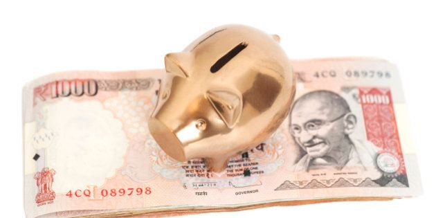 Golden piggy bank on indian 1000 rupee isolated on