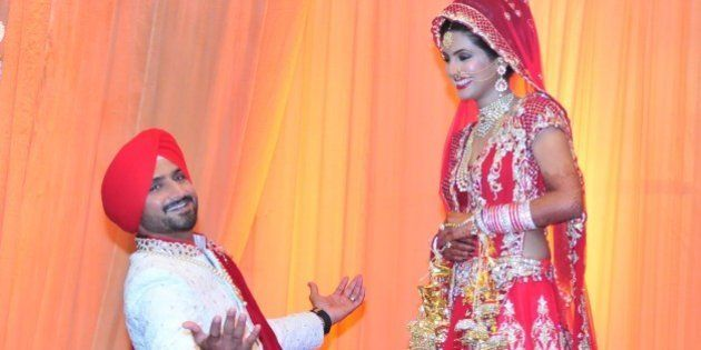 JALANDHAR, INDIA - OCTOBER 29: The newly wedded couple Indian cricketer Harbhajan Singh got on his knees...