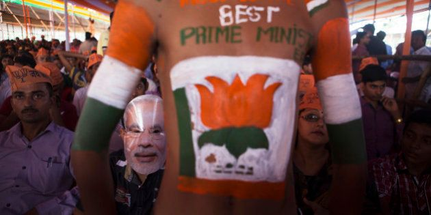 A supporter of the Bharatiya Janata Party (BJP), second left, wears a mask of Indian Prime Minister Narendra...