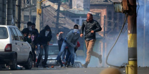 INDIA - 2015/10/30: Kashmiri Muslim protesters throw stones at Indian police during clashes in old Srinagar...