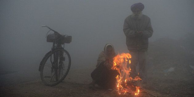 Indian farmers warm themselves around a fire during a dense fog along the India-Pakistan border in Suchit-Garh,...