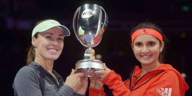 Martina Hingis of Switzerland, left, and Sania Mirza of India, right, pose with their trophy after they...