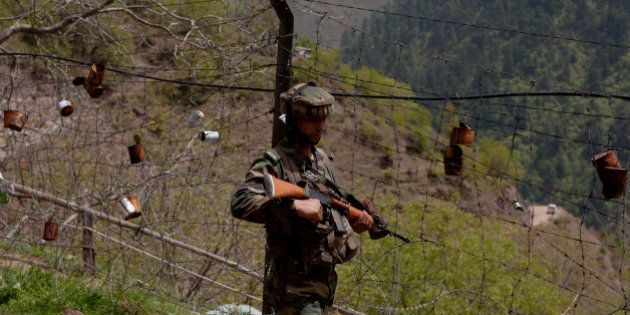 GOHALAN, KASHMIR, INDIA - APRIL 20: An Indian army soldier patrols the fenced area of Line Of Control...