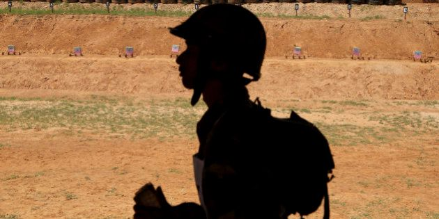 An Indian army soldier walks past a writing on the