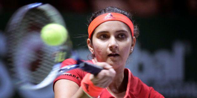 Sania Mirza of India makes a forehand return as she and partner Martina Hingis of Switzerland play Timea...