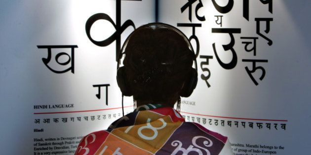 A woman listens to explanations on headphones about the Indian languages Hindi, left, and Marathi at...