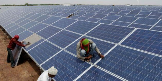 Indian workers install solar panels at the Gujarat Solar Park at Charanka in Patan district, about 250...