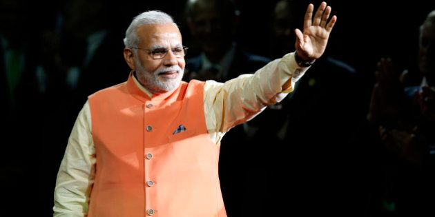 Prime Minister Narendra Modi of India waves to the crowd as he arrives to give a speech during a reception...