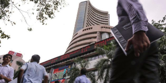 People walk by an electronic ticker board that indicates stock figures at the Bombay Stock Exchange (BSE)...