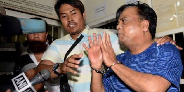 Indian national Rajendra Sadashiv Nikalje, 55, known in India as Chhota Rajan, (R) is held by Indonesian...