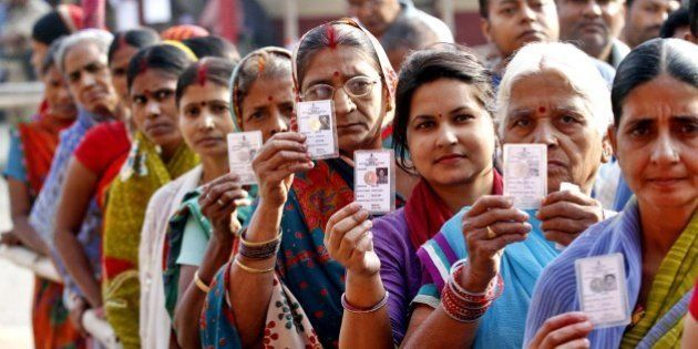PATNA, INDIA - OCTOBER 28: Voters pose with their ID Cards standing in queue to cast their votes at DAV...