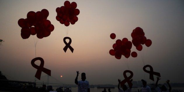 Indian social activists and children release ribbons and balloons during an event to mark World AIDS...