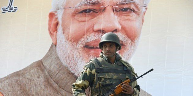 An Indian Border Security Force (BSF) soldier stands guard alongside a poster bearing the image of Indian...