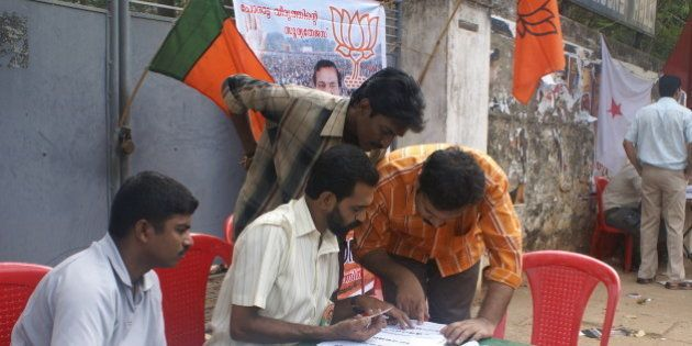 Party workers help voters identify their voting stations in Thiruvanathapuram, Kerala.The workers are...
