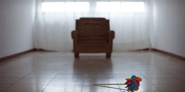 Toy windmill lying on floor of an empty room with sofa and two windows on