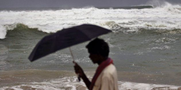 An Indian local villager walks with his umbrella at Gopalpur beach in Ganjam district 215 kilometers...