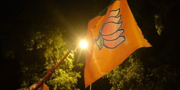 Indian Bharatiya Janata Party (BJP) supporters hold up a flag with the lotus party symbol outside the...