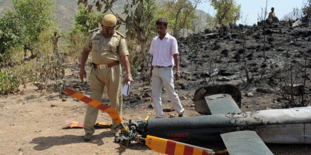 An Indian policeman (L) and a technician from Pawan Hans Helicoptre company collect evidence at the site...