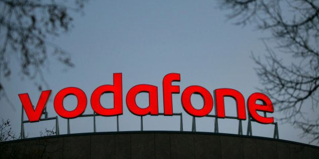 The Vodafone logo sits illuminated on top of the Vodafone Group Plc regional offices in Berlin, Germany,...