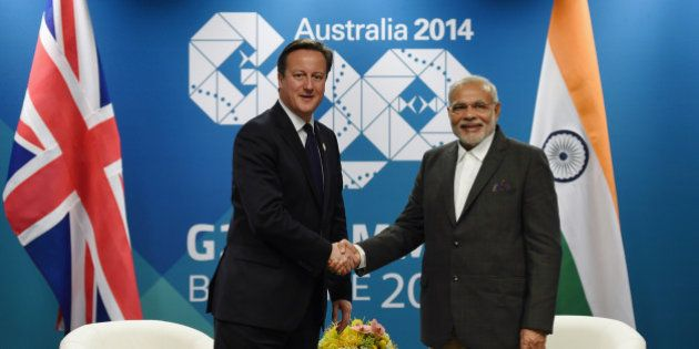 British Prime Minister David Cameron, left, shakes hands with Indian Prime Minister Narendra Modi during...