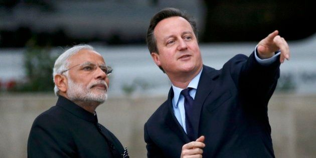 Britain's Prime Minister David Cameron, right, and India's Prime Minister Narendra Modi watch a flypast...