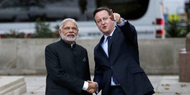 Britain's Prime Minister David Cameron (R) and India's Prime Minister Narendra Modi (L) watch a flypast...