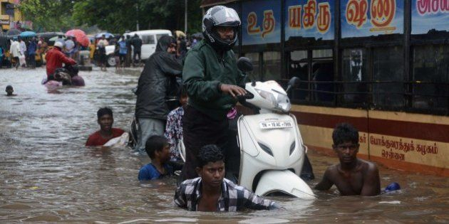 Indian men make their way on a flooded street in Chennai on November 9, 2015 following heavy rain from...