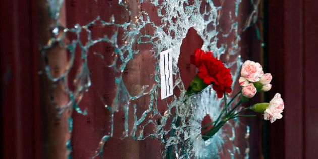Flowers are set in a window shattered by a bullet at the Carillon cafe in Paris, France, Sunday Nov....