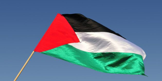 The Palestinian state flag waves in the wind with blue sky