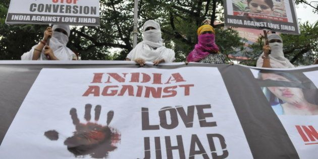 BHOPAL, INDIA - SEPTEMBER 12: Women associated with India Against Love Jihad hold placards and form a human chain to protest against love jihad and conversion to Islam at MP Nagar on September 12, 2014 in Bhopal, India. Hindu rightwing organizations claim that there is an Islamist strategy to convert Hindu women through seduction, marriage and money. (Photo by Mujeeb Faruqui/Hindustan Times via Getty Images)