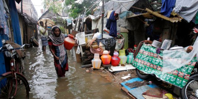 An Indian woman carries a vessel of water at a slum dwelling as it rains in Chennai, India, Friday, Nov....